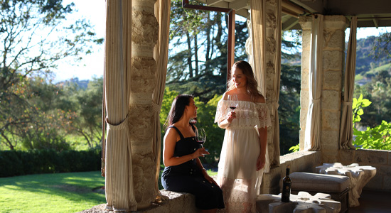 Women tasting wine on Manor House porch at Dusk
